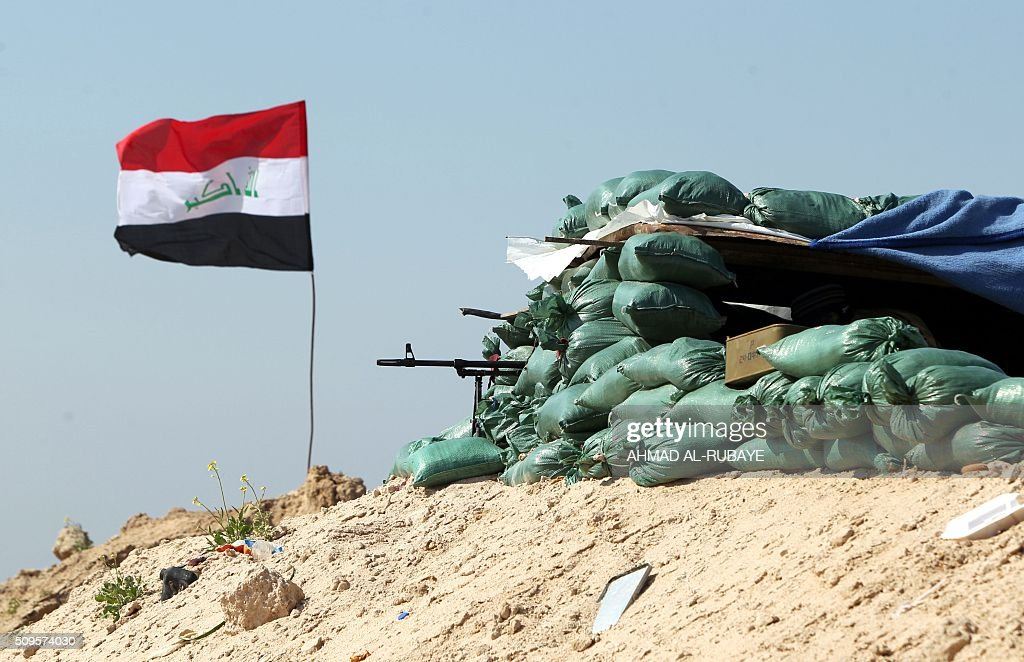 An Iraqi flag flies next to a look-out post held by Iraqi Shiite fighters from the Popular Mobilisation units, to monitor the frontline near the Tharthar lake, north of the city of Fallujah on February 11, 2016, as they continue to battle Islamic State group (IS) jihadists. RUBAYE