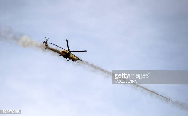 An Iraqi forces' Emergency Response Division Mil Mi28 'Havoc' attack helicopter fires missiles during the advance on the frontlines in west Mosul on...
