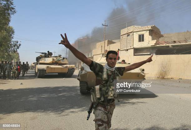 An Iraqi forces' fighter flashes the victory gesture as others backed by the Hashed AlShaabi advance through a street in the town of Tal Afar west of...