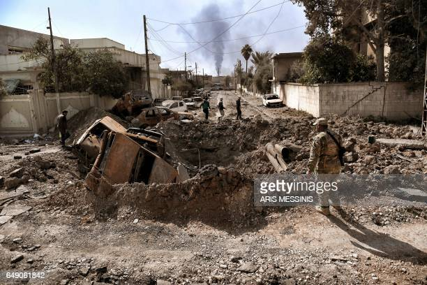 TOPSHOT An Iraqi forces member looks at a crater made by an air strike in west Mosul as Iraqi troops continue battling against Islamic State group...