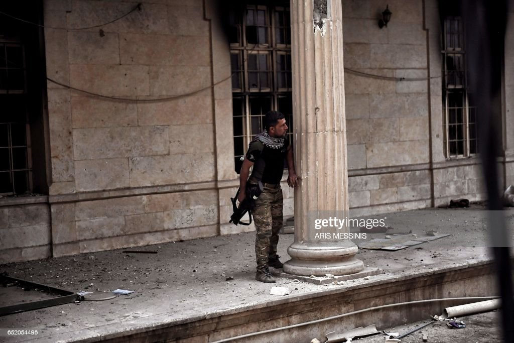 An Iraqi forces member takes cover outside the museum from fire during fighting with Islamic State (IS) jihadists in west Mosul on March 11, 2017 during the ongoing battle to retake the city from the group. /