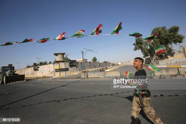 TOPSHOT An Iraqi forces member takes down Kurdish flags as they advance towards the centre of Kirkuk during an operation against Kurdish fighters on...