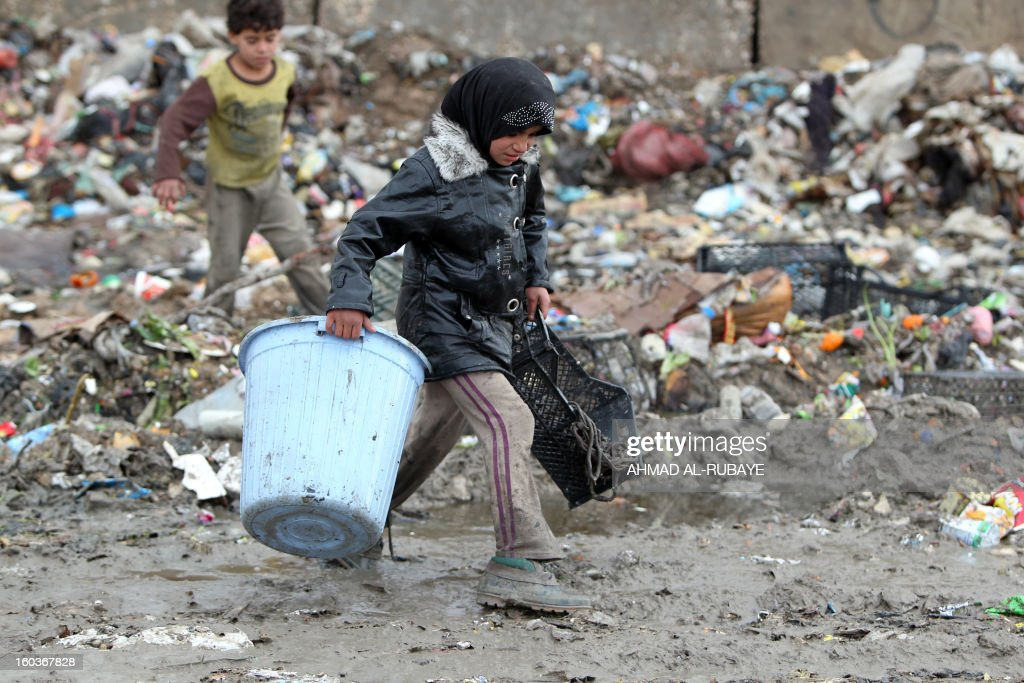 An Iraqi girl collects plastic boxes from a garbage dump on the outskirts of Baghdad's impoverished district of Sadr City, January 30, 2013. Around a quarter of Iraq's population are estimated by the country's Planning Ministry to live in poverty, and many survive in vast refuge dumps where they search for subsistence, either via using disposed goods or finding items that can be handed to recycling plants for money. AFP PHOTO/AHMAD AL-RUBAYE