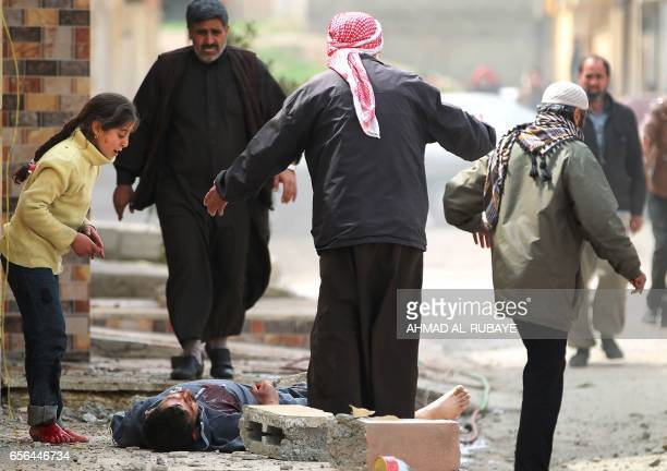 TOPSHOT An Iraqi girl cries over her father's body who was killed by a mortar shell fired by Islamic State group jihadists on civilians who were...