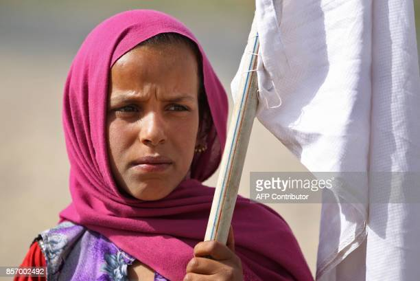 An Iraqi girl displaced from the outskirts of Islamic State group stronghold Hawija raises a white flag while travelling with family members and a...
