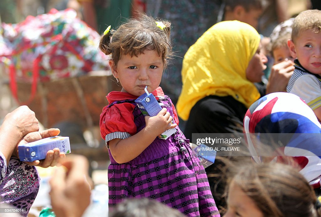 An Iraqi girl drinks juice near al-Sejar village, in Iraq's Anbar province, after fleeing with her family the city of Fallujah, on May 27, 2016, during a major operation by Pro-government forces to retake the city of Fallujah, from the Islamic State (IS) group. Hundreds of people fled the Fallujah area with the help of Iraqi forces, officials said. / AFP / AHMAD