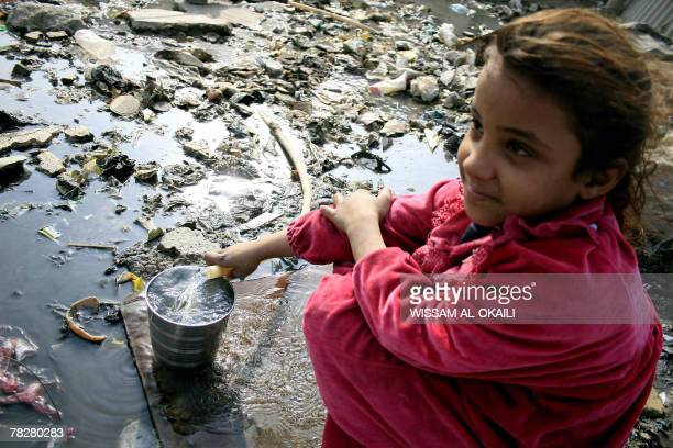 An Iraqi girl fills a tin with drinking water from a water pipe crossing an uncovered sewage canal at the area of Fdailiyah southeast of Baghdad 06...