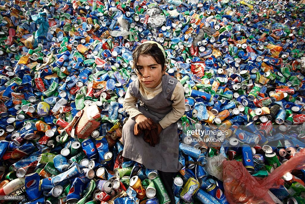 An Iraqi girl from an impoverished family searches through garbage for recyclable items at a waste dump on the outskirts of the shrine city of Najaf, on February 6, 2016. / AFP / HAIDAR HAMDANI
