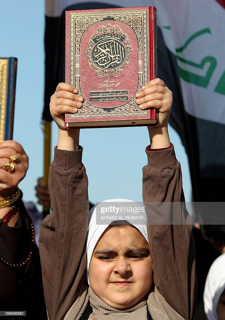 An Iraqi girl holds a copy of the Koran, Islam's holy book, during an anti-government protest outside the Sunni Umm al-Qura mosque in Baghdad on January 11, 2013. Thousands of Sunni Muslims took to the streets of Baghdad and other parts of Iraq to decry the alleged targeting of their minority, in rallies hardening opposition to the country's Shiite leader.