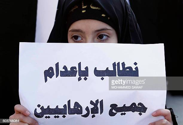An Iraqi girl holds a poster reading in Arabic 'We demand for the execution of terrorists' during a demonstration against the execution of prominent...