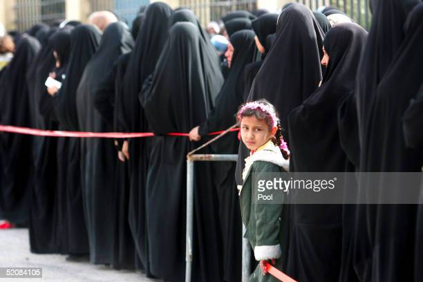 An Iraqi girl looks out of the womens queue at a polling station setup in a school January 30 2005 in Basra Iraq Iraqis started voting in their...