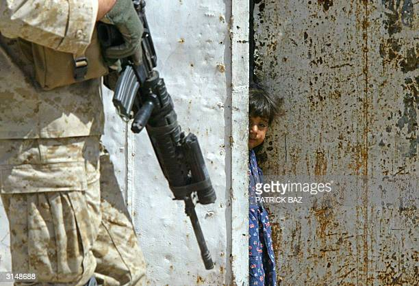 An Iraqi girl peers at US Marines from the 1st Marine Division patrolling the town of alNasr Wa alSalam near Fallujah 28 March 2004 Two days after...