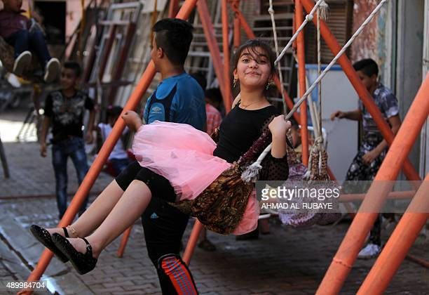 An Iraqi girl plays on a swing in the capital Baghdad on the second day of the Muslim Eid alAdha holiday on September 25 2015 Eid alAdha is...