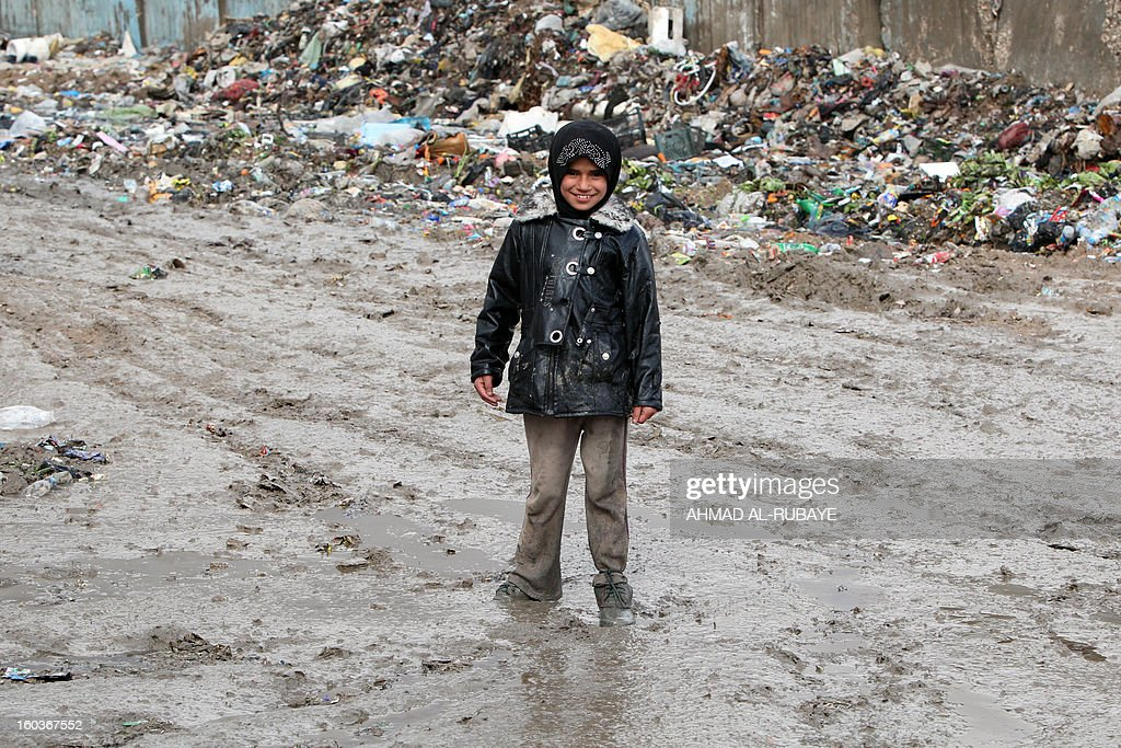 An Iraqi girl poses for a picture in muddy field used as a garbage dump on the outskirts of Baghdad's impoverished district of Sadr City, January 30, 2013. The UN has said Iraq is one of the countries in the Arab world most vulnerable to climate change, pointing to 'a higher frequency and intensity of extreme weather events and rising environmental degradation throughout the country.'