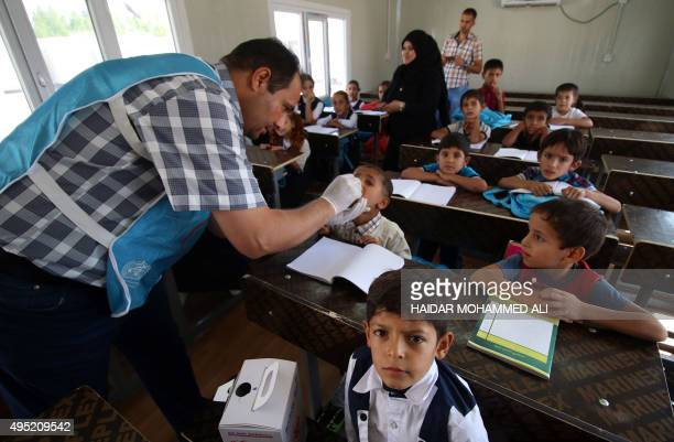 An Iraqi girl receives a dose of cholera vaccine at a school for internally displaced in southwest of the oil hub of Basra on November 1 during a...
