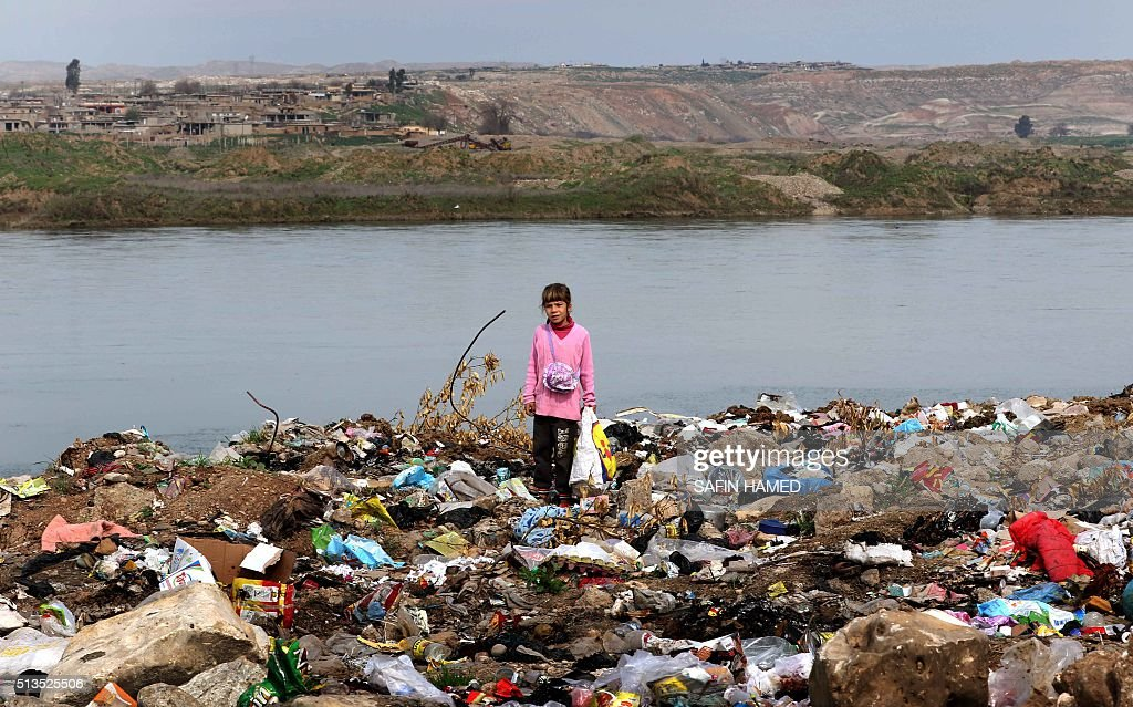 An Iraqi girl stands amid garbage on the banks of the Tigris River in the village of Wana some 10 kms south of the Mosul Dam near the city of Mosul...