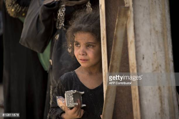 An Iraqi girl who fled the fighting between government forces and Islamic State group jihadists in the Old City of Mosul holds a jewellery box and...