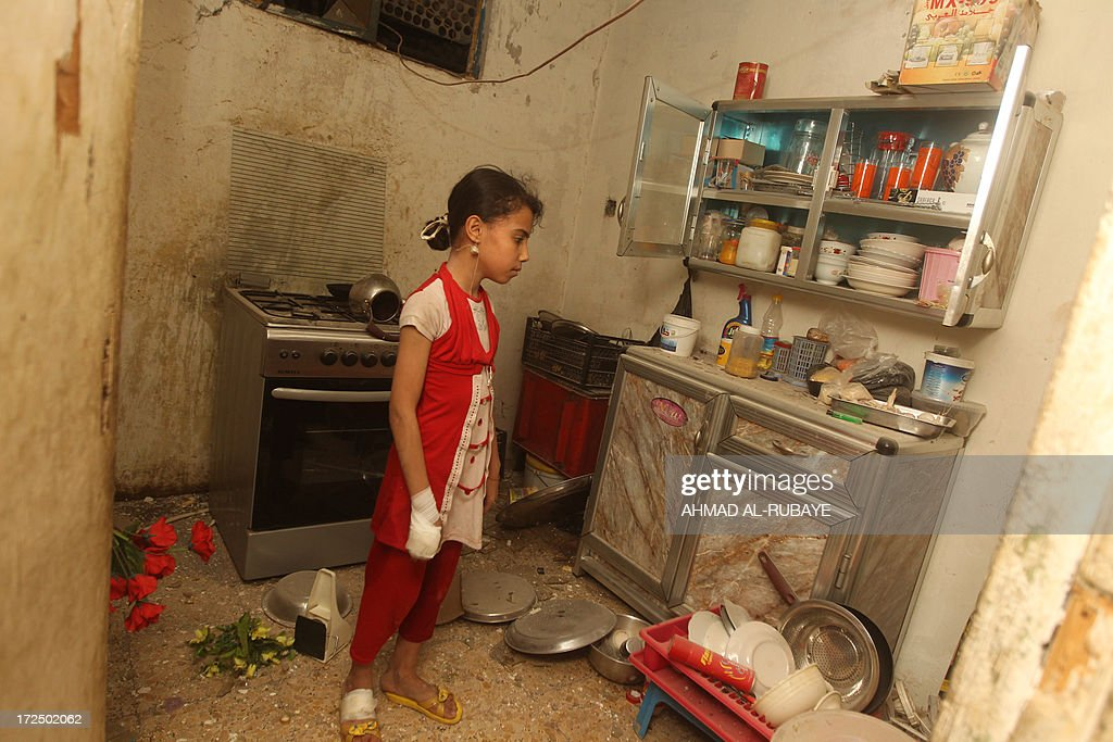 An Iraqi girl with her hand bandaged stands in the damaged kitchen of the family apartment following a car bomb explosion in the eastern Baghdad Kamaliyah district on July 2, 2013. A wave of attacks in Iraq, mostly targeting Shiite Muslims, including a spate of market bombings, killed 46 people on Tuesday, raising fears of a revival of the country's brutal sectarian conflict.
