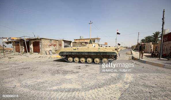 TOPSHOT An Iraqi government forces tank is positioned in the middle of the road as they secure the town of Sharqat around 80 kilometres south of the...