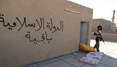 An Iraqi guman walks on September 10 2014 next to graffiti on the wall reading in Arabic 'the Islamic State is staying after government forces backed...