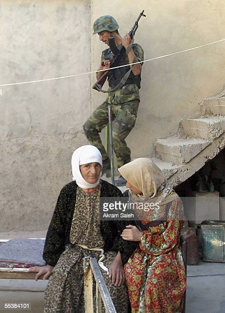 An Iraqi Interior Ministry commando of alBarq Brigade searches as Iraqi women sit in their house during housetohouse searches September 12 2005 in...