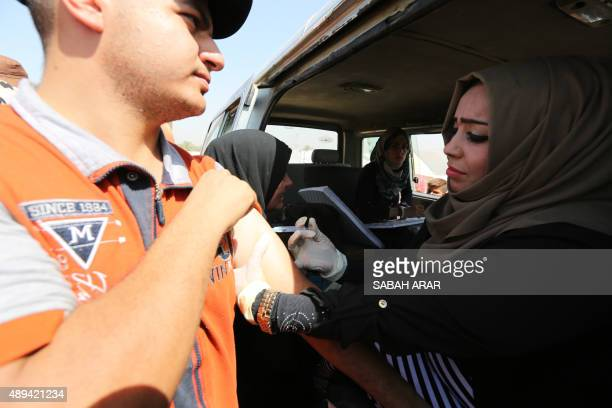 An Iraqi is vaccinated against cholera during a campaign at a makeshift camp housing displaced Iraqis who fled the violence in the Iraqi city of...