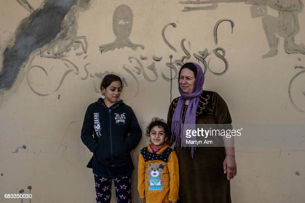 An Iraqi Kaka'i woman and two of her daughters stand in front of their family home in the village of Wardak in the Nineveh plains of northern Iraq...