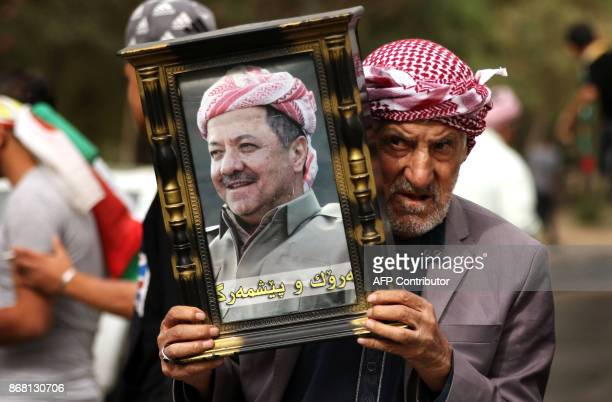 An Iraqi Kurd holds a frame portraying the Iraqi Kurdish leader Massud Barzani during a protest in support of him in Arbil the capital of autonomous...