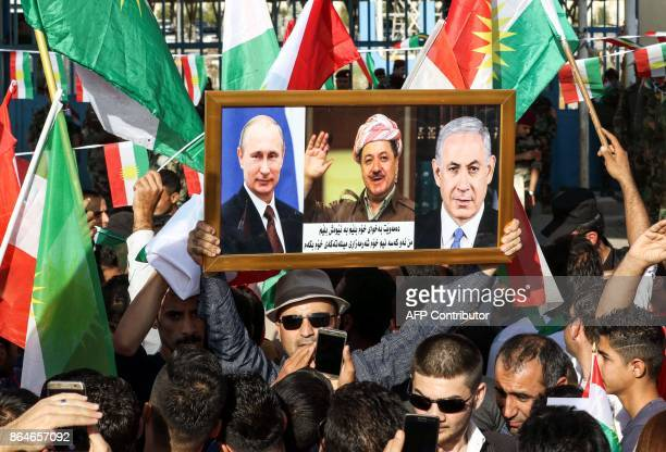 An Iraqi Kurd raises a frame showing the portraits of Russian President Vladimir Putin Israeli Prime Minister Bejamin Netanyahu and Iraqi Kurdistan...