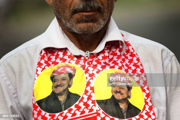 An Iraqi Kurd wears a scarf bearing a portrait of the Iraqi Kurdish leader Massud Barzani during a protest in support of him in Arbil the capital of...