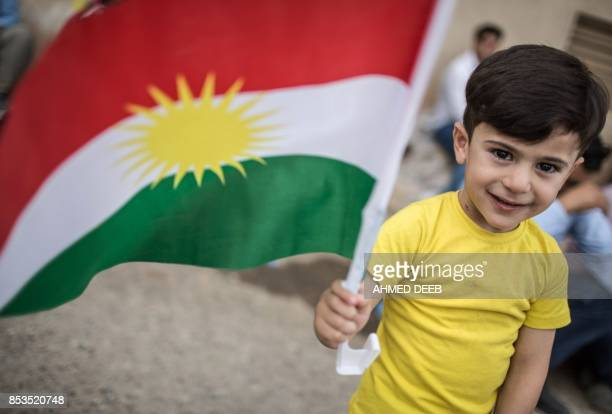 An Iraqi Kurdish boy holds a Kurdish flag at a school in Arbil which is being used as a polling station as voters cast their ballots in the Kurdish...