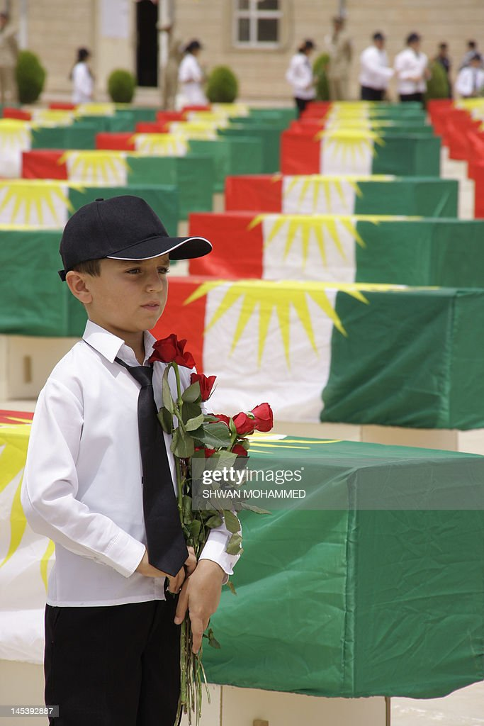 An Iraqi Kurdish boy stands with red roses in his hand next to coffins containing the remains of 730 people killed in the 1988 Anfal massacre, during a ceremony in Sulaimaniyah before their reburial in northern Iraq, on May 28, 2012. The coffins contain the remains of victims of the brutal 'Anfal' (Spoils of War) campaign carried out by Saddam Hussein's forces 24 years ago, in which an estimated 182,000 people have died.