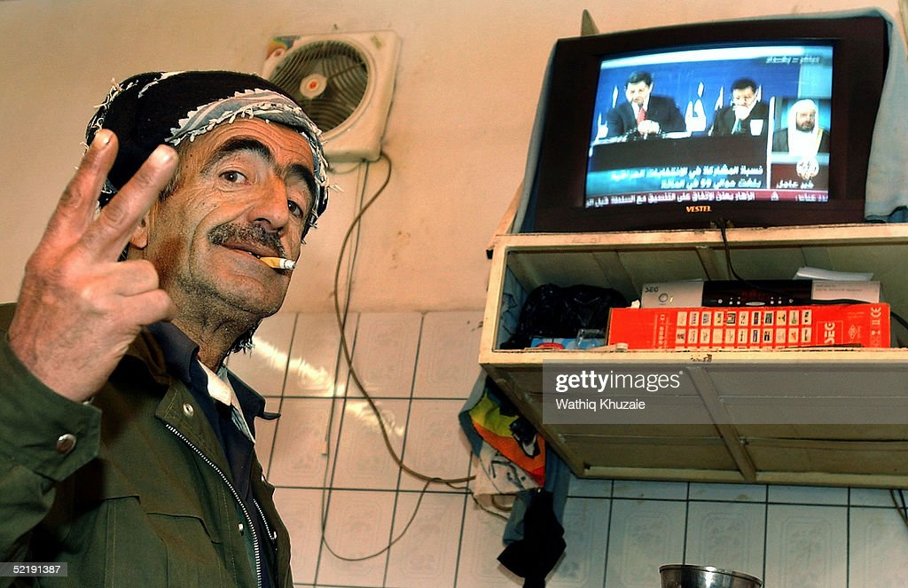 An Iraqi Kurdish elderly man makes number two in his hand in reference to the second position that the kurds got in the elections as he watches Iraqs...