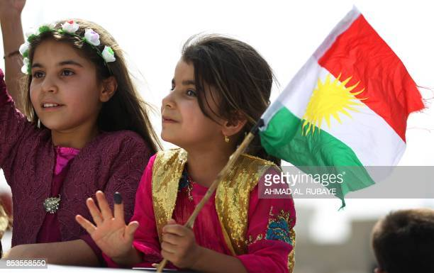 An Iraqi Kurdish girl celebrates with the Kurdish flag in the northern city of Kirkuk on September 25 2017 as Iraqi Kurds vote in a referendum on...