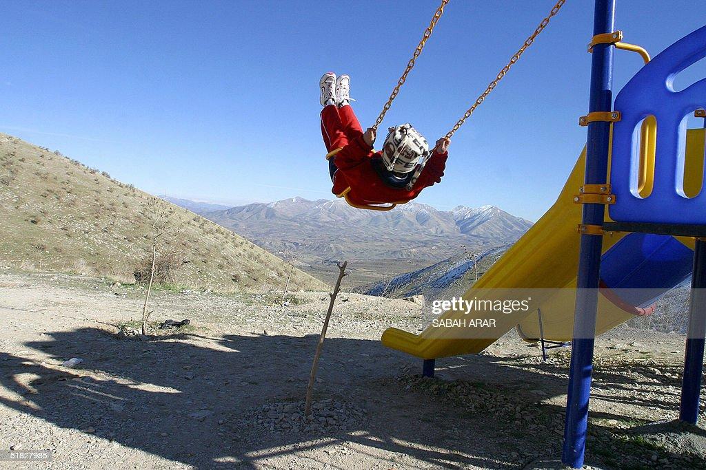 An Iraqi Kurdish girl swings at Azmar mountain north of the Iraqi Kurdistan city of Sulaimaniyah 350 kms northeast of Baghdad 05 December 2004 The...