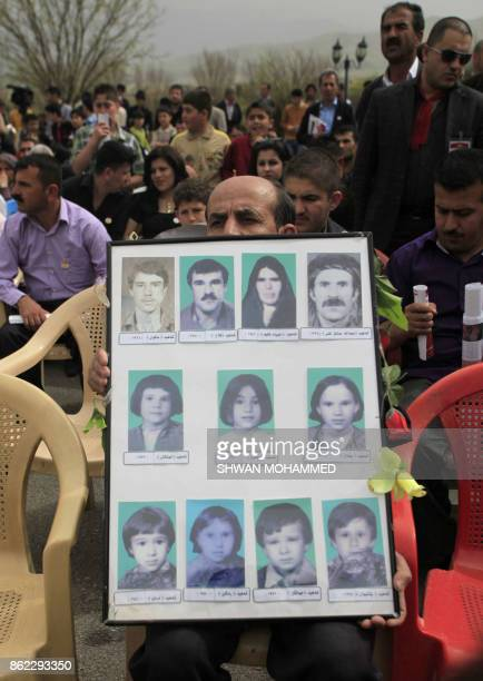 An Iraqi Kurdish man carries pictures of victims of the 1988 gas attacks during a ceremony marking the anniversary of the attacks in the Iraqi...