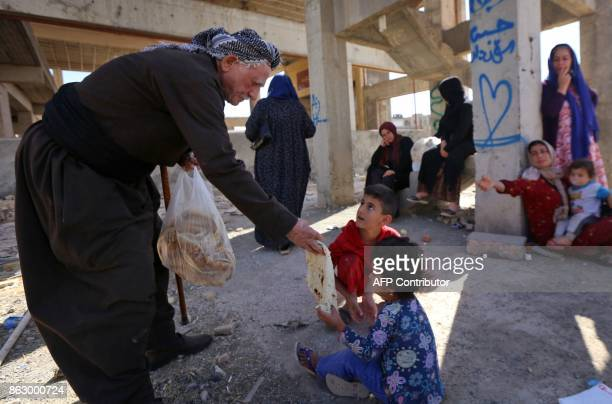 An Iraqi Kurdish man from Arbil distributes bread to a family fleeing violence in the northern Kirkuk province on October 19 2017 at an unfinished...