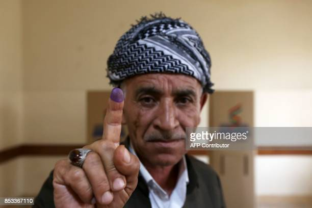TOPSHOT An Iraqi Kurdish man shows his inkstained finger after voting in the Kurdish independence referendum in Arbil the capital of the autonomous...