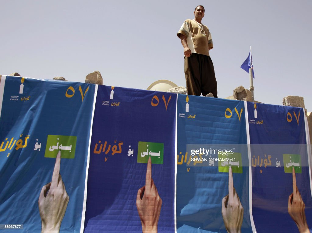An Iraqi Kurdish man stands on a wall draped with election posters in the northern city of Sulaimaniyah 330 kms from the Iraqi capital Baghdad on...
