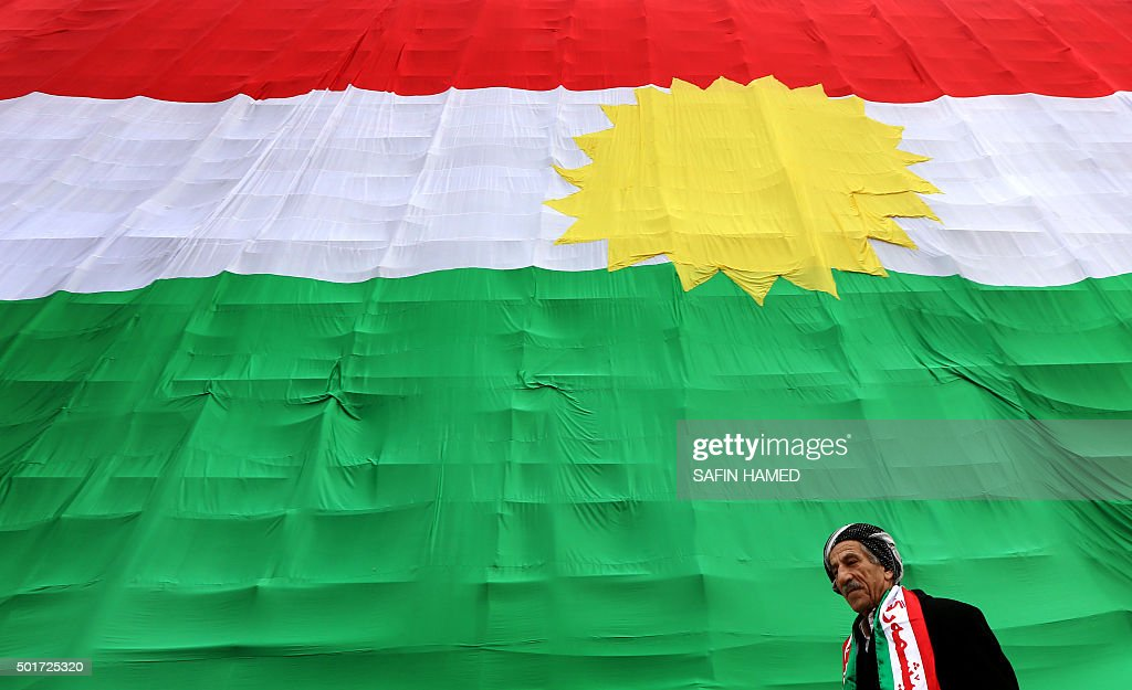 An Iraqi Kurdish man walks past a giant flag of Kurdistan as Kurds marked Flag Day on December 17 2015 in Arbil the capital of the autonomous Kurdish...