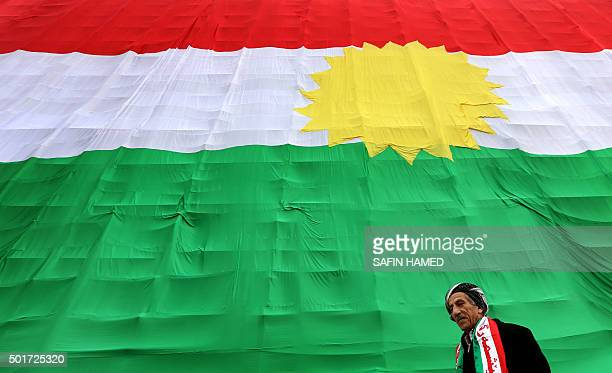 An Iraqi Kurdish man walks past a giant flag of Kurdistan as Kurds marked Flag Day on December 17 2015 in Arbil the capital of the autonomous Kurdish...