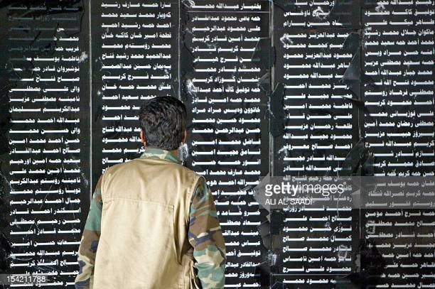 An Iraqi Kurdish militant looks at names of some 5000 civilians 08 May 2006 who were killed in a chemical attack by the by the regime of ousted...