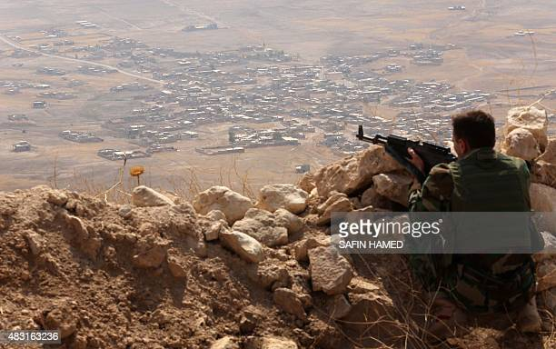 An Iraqi Kurdish Peshmerga fighter monitors his surrounding from the top of Mount Zardak about 25 kilometres east of Mosul on August 6 2015 AFP PHOTO...