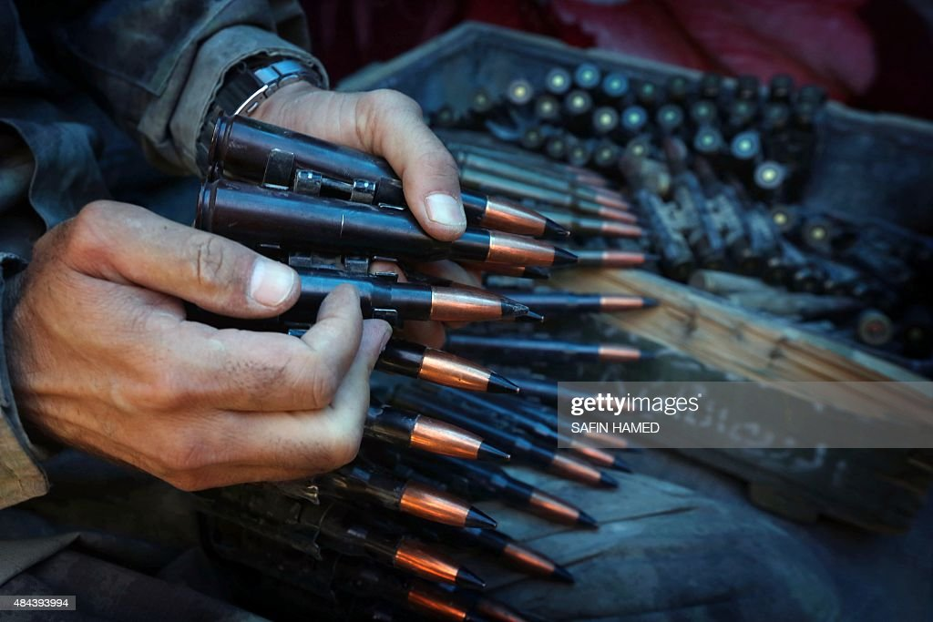 An Iraqi Kurdish Peshmerga fighter prepares an ammunition belt as he guards a position at the frontline of fighting against Islamic State (IS) group's militants near the northern Iraqi town of Sinjar, west of the city of Mosul on August 17, 2015.