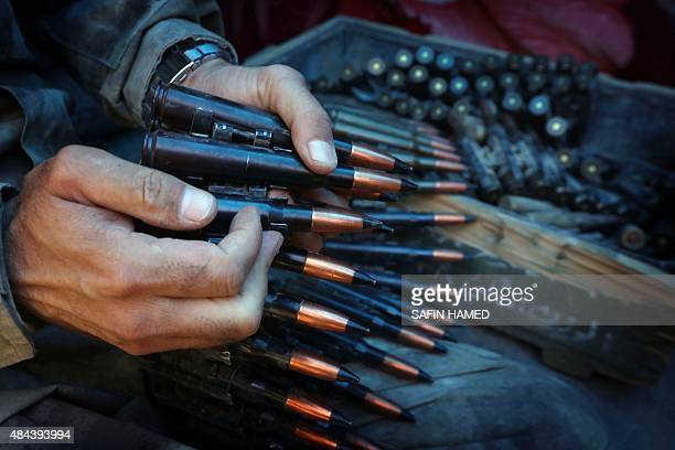 An Iraqi Kurdish Peshmerga fighter prepares an ammunition belt as he guards a position at the frontline of fighting against Islamic State group's...