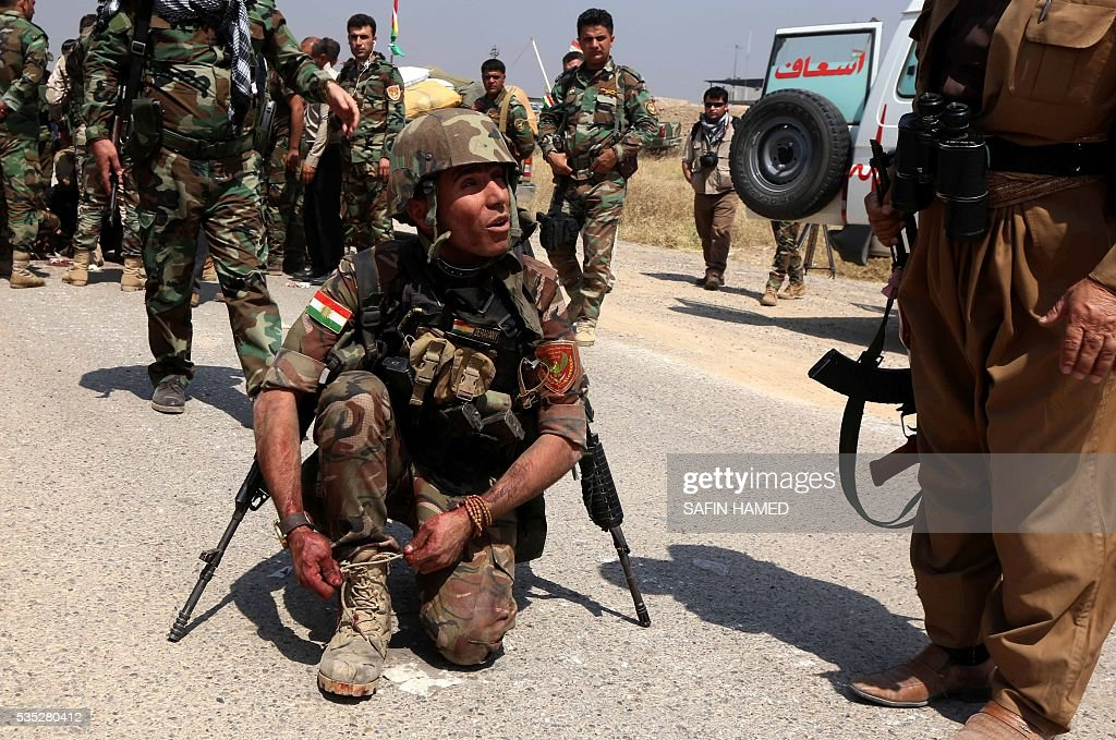An Iraqi Kurdish Peshmerga fighter ties up his shoelaces as others give treatment to a wounded comrade during an operation near Hasan Sham village, some 45 kilometres east of the city of Mosul, aimed at retaking areas from the Islamic State group on May 29, 2016. The 'peshmerga-led ground offensive, backed by international coalition warplanes' started before dawn, the Kurdistan Region Security Council (KRSC) said. The fresh push against the jihadist organisation comes a week after Iraqi forces launched an operation against Fallujah, IS's only other major urban hub in Iraq. / AFP / SAFIN