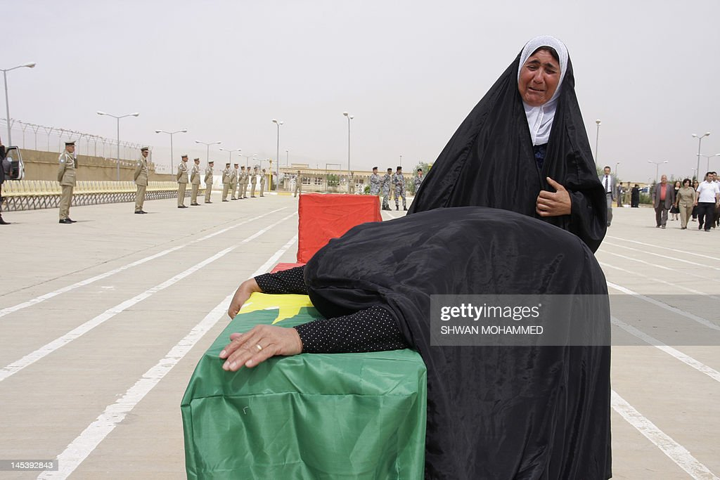 An Iraqi Kurdish woman mourns over a coffin containing the remains of a relative killed in the Anfal massacre, during a ceremony in Sulaimaniyah before their reburial in northern Iraq, on May 28, 2012. The coffins contain the remains of 730 victims of the brutal 1988 'Anfal' (Spoils of War) campaign carried out by Saddam Hussein's forces, in which an estimated 182,000 people have died.