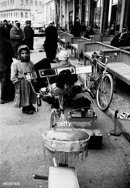 An Iraqi little girl observing a bicycle with mirrors trumpet bike horn bike bell and saddle with fringes parked outside a café Najaf December 1956
