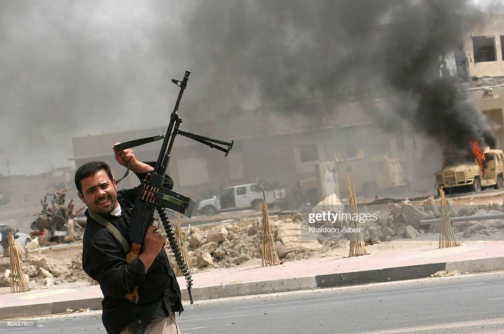 An Iraqi Madhi army militiaman dances near a burning Iraqi army vehicle after attacking it on March 30 2008 in the city of Basra 370 miles south of...