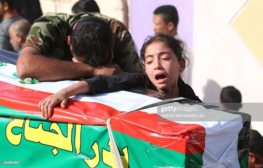 An Iraqi man and a girl mourn over the coffin of a relative who was killed fighting alongside Iraq government forces to retake to city of Fallujah from jihadists of the Islamic State group, on May 25, 2016 during a funeral in the southern city of Basra. Iraqi forces battled the Islamic State group in the opening stages of an operation to retake Fallujah, one of the toughest targets yet in Baghdad's war against the jihadists. ALI